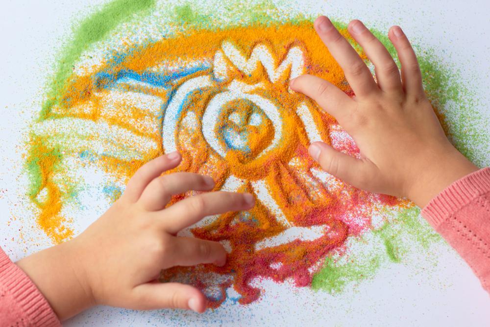enfant qui dessine dans du sable colore